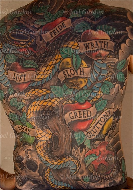 Close up of tattoos on back of the &quot;Seven Deadly Sins&quot;: Pride, Wrath, Lust, Sloth, Envy, Greed, Gluttony.<br />