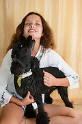 A young female teen of 14, plays with her pet poodle dog. The dog is licking her face. Model Release Available