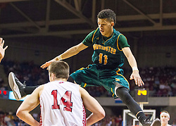 Huntington guard Tavian Dunn-Martin (11) gets caught in the air defending Hurricane forward Brandon Ford (14) during a semi-final game at the Charleston Civic Center.