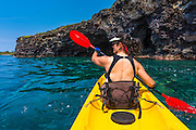 Woman kayaking along the Kona Coast, The Big Island, Hawaii USA