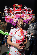 New York, NY, USA-27 March 2016. An Asian woman wearing a floral print cheongsam wears a hat topped with a palanquin bearing an Easter bunny, and carried by more bunnies in annual Easter Bonnet Parade and Festival.