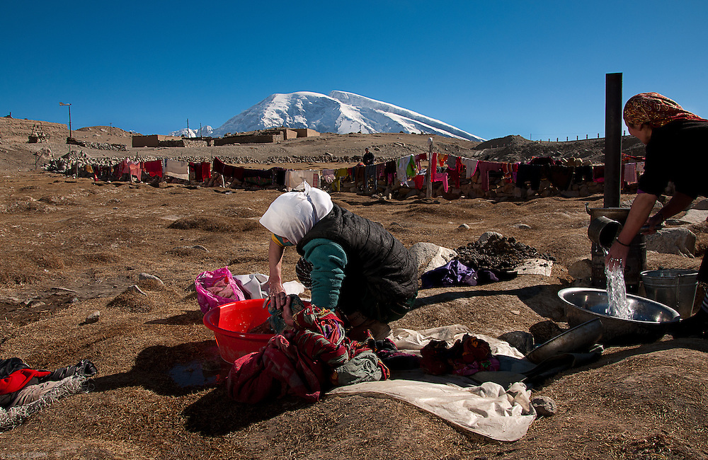 — In the shadow of Muztagh-Ata Mountain, women wash their families' clothes in water warmed on a pot-belly stove, fueled with manure.