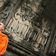 Angkor, Siem Reap Province, Cambodia: The temple complex at Angkor Wat was built by King Suryavarman II  in the early 12th century as his state temple and capital city. As the best-preserved temple at the site, it is the only one to have remained a significant religious centre since its beginning, first Hindu, dedicated to the god Vishnu, then Buddhist. The temple is a classical style of Khmer architecture.  A Buddhist monk stands in front of a relief of Apsaras. Jose More Photography