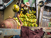 "10 JUNE 2014 - YANGON, MYANMAR:   Porters unload coconuts from a riverboat on the banana jetty. The ""banana jetty"" is on the Yangon River north of central Yangon on Strand Road. Bananas, coconuts and other fruit are brought in here from upcountry, sold and reshipped to other parts of Myanmar (Burma). All of the labor here is done by hand. Porters carry the produce to the jetty and porters load the boats before they steam upriver.   PHOTO BY JACK KURTZ"