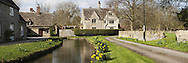 The River Thames as it flows through Church Walk in the Cotswold Village of Ashton Keynes in Wiltshire, Uk