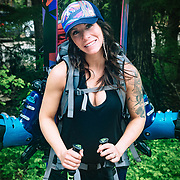 Portrait of professional photographer Shannon Mahre (six months pregnant) with loaded backpack.