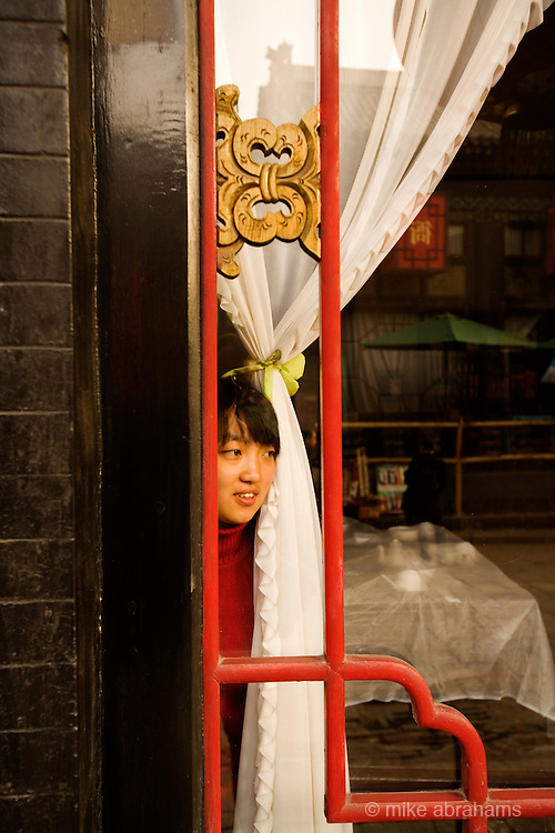 A waitress looks out of the window of a restaurant in Pingyao, People's Republic of China