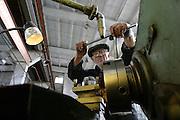 """In der maroden Farbrik für """"vibrierende Maschinen"""" montiert ein Arbeiter Metallteile. Südossetien erklärte sich 1990 selbsständig und konnte den folgenden Sezessionskrieg gegen die Georgier für sich entscheiden. Zwischen Georgien und der abtrünnigen Region, die den Anschluß an die Russische Förderation fordert, kommt es trotz des Waffenstillstandsabkommens von 1992 immer wieder zu bewaffneten Ausseinandersetzungen. (In the run down fabication of """"vibrating machines"""" mount a worker stuff. South Ossetia is a de facto independent republic located within the internationally recognized borders of Georgia. Although this former Soviet autonomous region has declared its independence in 1990. After the following civil war between georgians and ossetians ends in 1992, most parts of the territory is ossetian controlled, while some villages with georgian population are administrated by an georgian """"Alternative Government"""".)"""