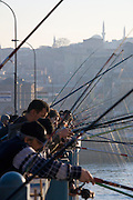 Istanbul. Fishermen on Galata Bridge at the entrance of the Golden Horn (Halic?) in the late afternoon.