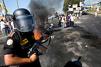 A special anti riot police officer armed with a tear gas gun stands guard in front of burning tires Tuesday Sept. 11, 2007, Palin Guatemala. A angry mob took to the streets and went on to burn down the mayors office as well as his home in demonstration after and clash with local police on the previous day. Residents accuse the mayor of, among other things, of bussing voters for the elections on Sept. 9 2007.   (photo by/ Darren Hauck).....