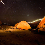 Stars light up the evening sky and headlamps track through camp on the Shira Plateau, Machame Route, Kilimanjaro, Tanzania.