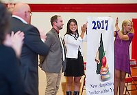 Laconia High School's Tate Aldrich receives a standing ovation after being named 2017 New Hampshire Teacher of the Year on Friday afternoon. Holding the 2017 sign are 2015's Liz Lichtenberg and 2016's Ashley Preston.   (Karen Bobotas/for the Laconia Daily Sun)