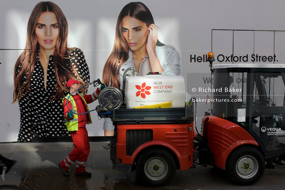 Street cleaner from contractor Veolia winds up hose after hosing down waste bin in Oxford Street, central London.