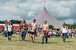 © Licensed to London News Pictures. 22/08/2014. Reading, UK.   Topless Festival goers enjoy the sun at Reading Festival 2014 on Friday, the opening day.    The weather is sunny with light cloud.   Today is expected to remain dry with a 25% risk of showers.  Photo credit : Richard Isaac/LNP