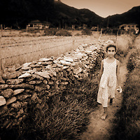 A young girl walks through a field on a path lined with stone and barbed wire