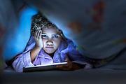 Portrait of cute girl using digital tablet under blanket in bed