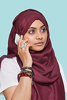 Young Muslim woman in traditional clothing using cell phone against blue background