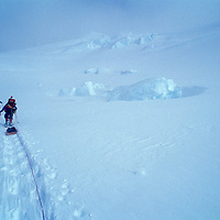 USA, Alaska, Denali National Park, (MR) Climbers snowshoe with heavy packs up Kahiltna Glacier on Mt. McKinley West Buttress