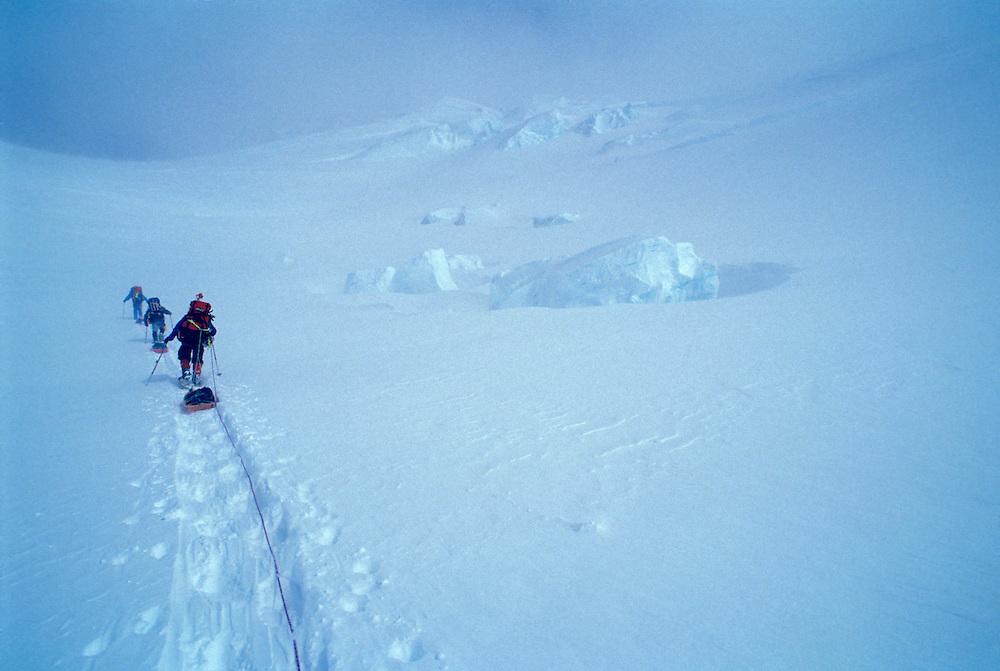 USA, Alaska, Denali National Park, (MR) Climbers snowshoe with heavy packs up Kahiltna Glacier on Mt. McKinley West Buttress