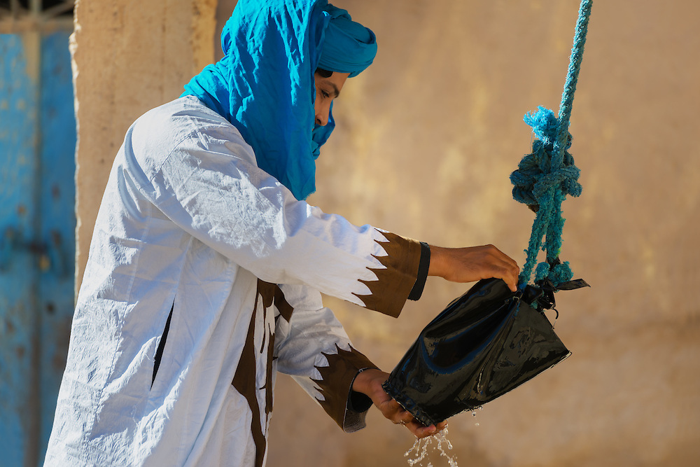 Traditional dressed man gets water from a well, Erfoud, Morocco.