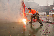 A worker sets off a pole draped in hundreds of firecrackers.