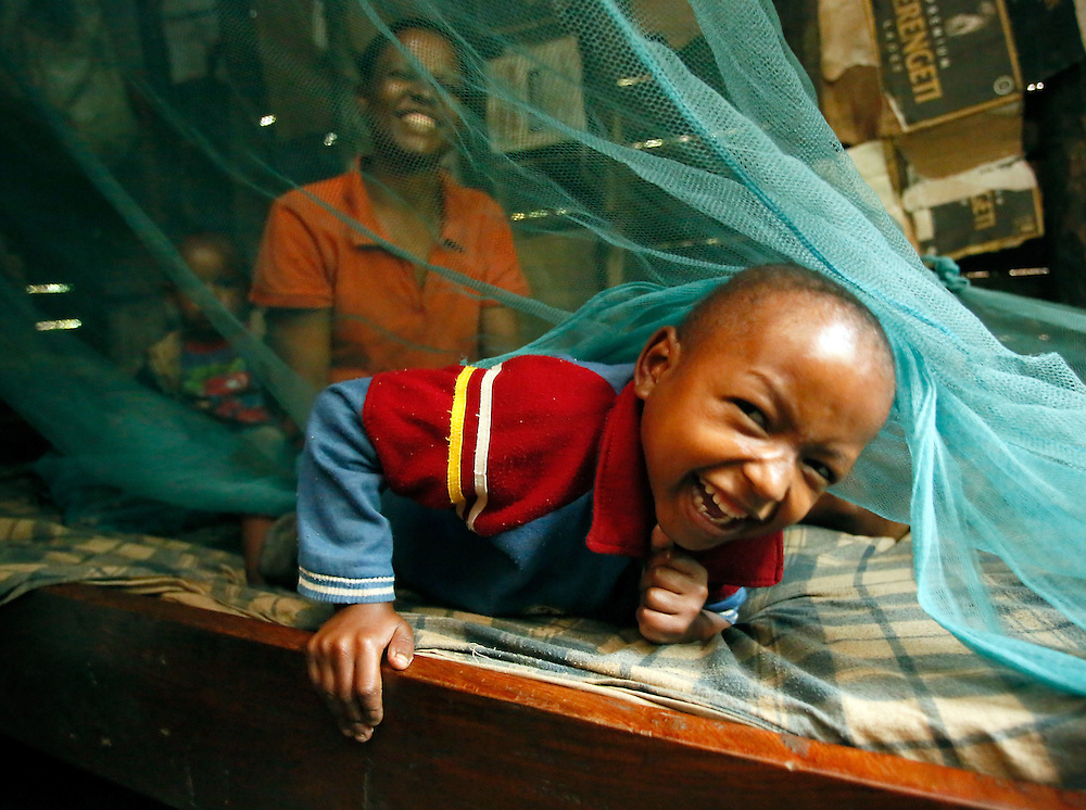 "Elihuruma Koka, 6, peeks out from under a bed net as his mother Pamela Timotheo Koka and sister Mary, 1, look on, in Marangu, a village in the foothills of Mt. Kilimanjaro, Tanzania, Friday, Aug. 10, 2012.  Koka received her net free through a Tanzania government program as part of her pre-natal care. Volunteers from the local Lutheran parish check on Pamela and her family every month to make sure that they are using their nets correctly and that no one has symptoms of malaria. Before she had bed nets, Koka and her son frequently suffered the tell-tale signs of the disease, such as fever and weakness. Now that they are healthy Koka sings in the church choir and harvest bananas and tends her chickens while Elihuruma attends Lutheran Montessori school. ""I sleep well when I know the mosquitos aren't biting us"". The United Nations Foundation supports malaria education efforts such as these, coordinated by faith based partners like the Lutheran Malaria Initiative. (Stuart Ramson/Insider Images for UN Foundation)"