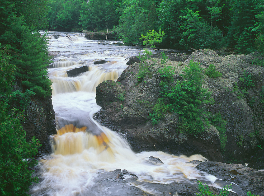 Potato River Falls, with its brown water rich in tannins, cuts through volcanic rock in northern Wisconsin. Summer. Morning.