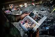 A Kurdish Peshmerga soldier views the photo album of a Yazidi family which was found in the burnt out ruins of their home. The fate of the family is uncertain. Bashiqa, Iraq. Nov. 20, 2016. (Photo by Gabriel Romero ©2016)
