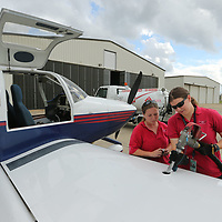 Tffany Heavner, left, and Cortney Norman fill the wing tank with fuel while the pilot checks the weather at the Tupelo airport.