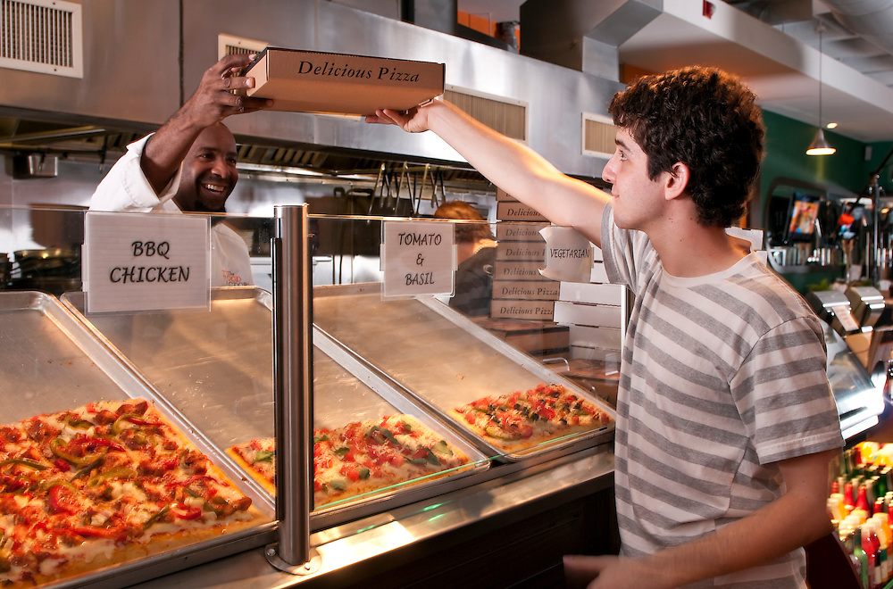 Young guy buys a pizza in a modern restaurant