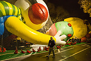 New York, NY – 27 November 2019. Thousands of spectators packed the streets around the American Museum of Natural History to see the inflation area for the balloons for Macy's Thanksgiving Day Parade. A worker walks by the Wimpy Kid, held down with nets and weight bags.