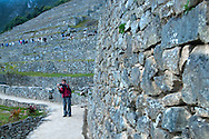 A tourist takes a photo at Machu Picchu in front of the famed terraces of the Incas just before full sunrise on the winter solstice of 2012.
