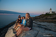 Apogee tour group taking in the sunrise at Pemaquid Point Lighthouse on Maine Coast trip in New Harbor, Maine, USA