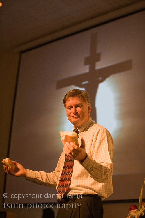 Senior Pastor John Teschan giving thanks for the bread at the first communion and service in the new Evangelical Church of Bangkok (ECB) Fellowship Hall in Bangkok, Thailand