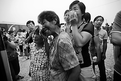 Relatives of a migrant villager of Cangfang town bade tearful farewells as she board the bus for relocation to neighbouring Hui county to neigbouring Hui county, more than 500 kilometers away, to make way for the colossal South-to-North Water Transfer project in Xichuan county of Henan Province in China on 29 June 2010. The South-to-North Water Transfer project, the largest known water diversion project, was conceived in 1952 to solve the country's chronic water shortages and involves creating three routes to channel 44.8 billion cu m of water from southern China to the northern areas. As part of the project's central route, affecting Henan and Hubei provinces, water from the Danjiangkou reservoir will be diverted to Beijing. The central route, which will raise the height of the Danjiangkou reservoir dam from 162 meters to 176.6 meters, requires the relocation of 330,000 people in Henan and Hubei provinces. Parts of Xichuan county, a remote, mountainous region inaccessible by railway and home to 162,000 migrants, the most anywhere, will be completely submerged by water from the Danjiangkou reservoir by 2014. The vast resettlement of affected residents in Xichuan county began in August 2009 and lasted till 2011.