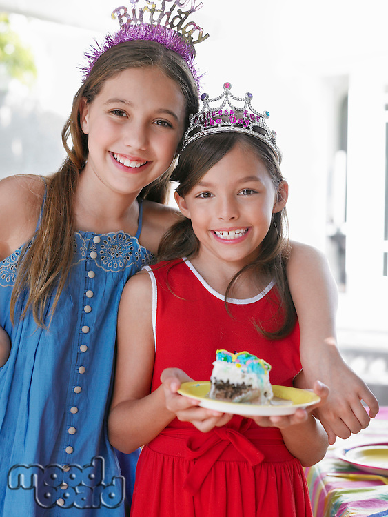 Portrait of two girls (7-9 10-12) in tiaras one holding plate with cake smiling