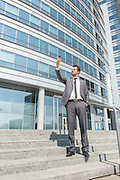 Full length of businessman taking selfie on steps outside office