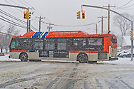 Merrick, New York, U.S. January 21, 2014. A Nassau Inter-County Express NICE bus crosses an intersection as snow falls heavily on Long Island. Governor Cuomo declared a state of emergency due to the snow storm, with up to 10 inches of snow expected.