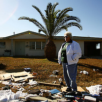 LEHIGH ACRES, FL -- January 23, 2009 -- Gloria Chilson stands outside of her fomer home of 18 years, where her belongings were tossed out into the yard during foreclosure, in Lehigh Acres, Fla., on Friday, January 23, 2009.  Lehigh Acres has become a symbol for the fallen American Dream - with only two years separating itself from housing market boomtown to a current landscape of abandoned developments and struggling businesses.