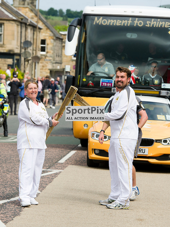 Neil Allan from Edinburgh passes the baton onto Leslie Glidden on Day 27 of the Olympic Torch relay and the carnival continues it's travel to London heading through Milton Bridge and Penicuik in Midlothian. 14 June 2012 (Ger Harley | STOCKPIX)