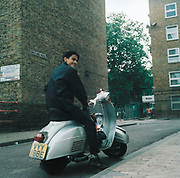 Teenage boy sitting on a scooter outside a housing estate in the East End