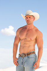 muscular cowboy without a shirt outdoors