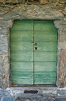 Old green wooden door in a stone wall in Minusio, Ticino, Southern Switzerland.