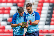 Adam Roscrow (#10) and Luke O'Neill (#2) of AFC Wimbledon look at the match programme before the EFL Sky Bet League 1 match between Sunderland and AFC Wimbledon at the Stadium Of Light, Sunderland, England on 24 August 2019.