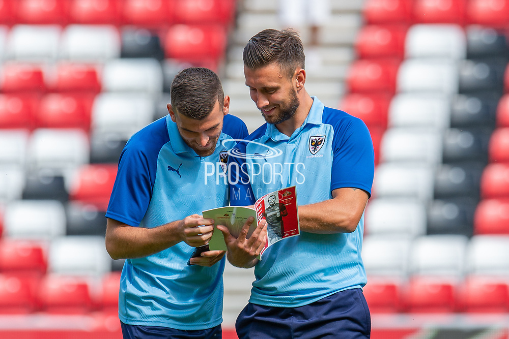 Adam Roscrow (#10) and Luke O'Neill (#2) of AFC Wimbledon look at the match programme before the EFL Sky Bet League 1 match between Sunderland and AFC Wimbledon at the Stadium Of Light, Sunderland, England on 24 August 2019.