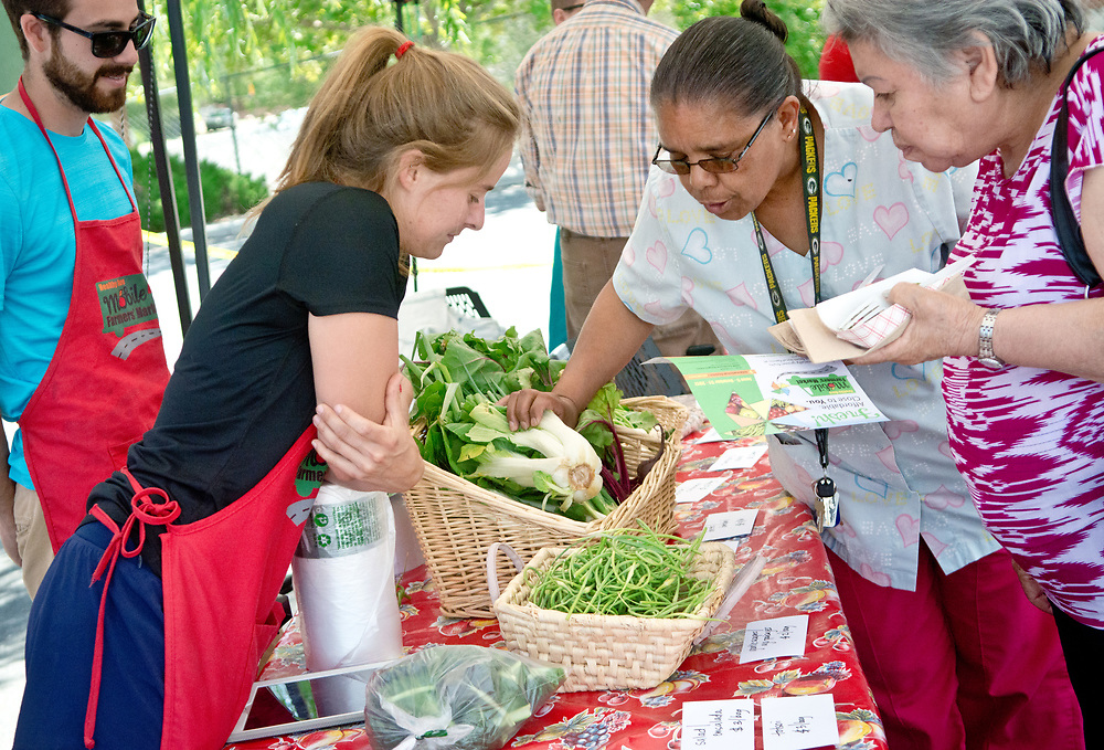 Natalie Donnelly, community food projects coordinator with Presbyteriean Center for Community Health, front left, talks to Leticia Arango, second from right, and Manuela Tena, right, about bok choy and some of the other produce for sale at the Mobile Farmers' Market, Tuesday, June 6, 2017. The market made three stops, including one outside of Presbyterian Medical Group at 3436 Isleta Blvd. SW.  (Marla Brose/Albuquerque Journal)