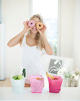 Happy woman holding donuts in front of eyes at kitchen counter