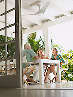 Three people sitting at verandah table low angle view