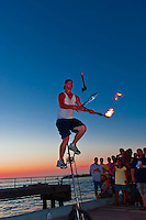 Street busker juggling fire, sharp knives and axe at sunset celebration, Mallory Square, Key West, Florida Keys, Florida USA