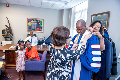 University President Wayne A.I. Frederick putting on a medal with the University